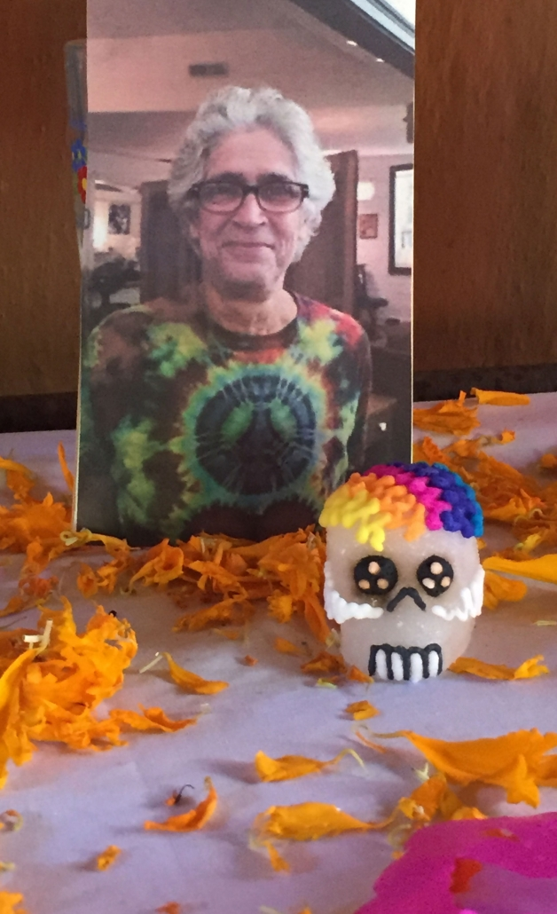 Day of the dead rainbow sugar skull next to Steven's photo on a beautiful dia de los Muertos alter to celebrate his life on day of the dead.