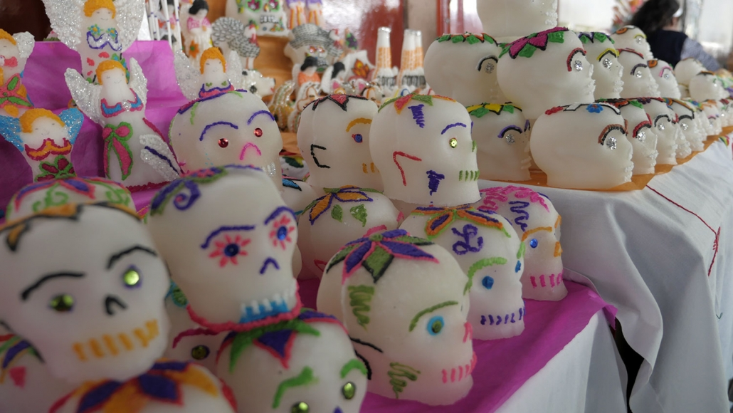 Hundreds of sugar skulls lined up on tables for sale. Families living in Mexico buy these sugar skulls and write the name of the person who died so they can celebrate their lives on Day of the Dead